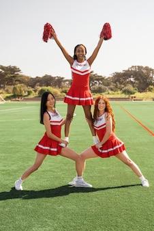 Des pom-pom girls complètes qui s'entraînent ensemble
