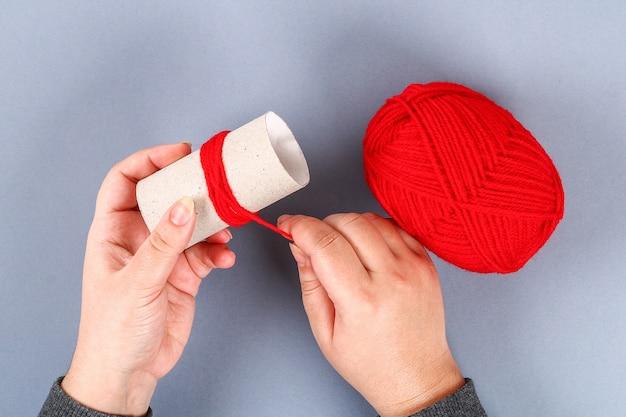 Pom pom rouge fait main bricolage monstre de fil, chenille découle en forme de coeur.