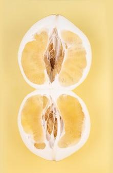 Pomelo frais jaune coupé en deux moitiés, gros plan.