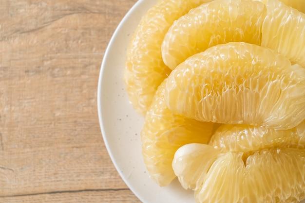Pomelo frais pelé, pamplemousse ou shaddock sur plaque blanche