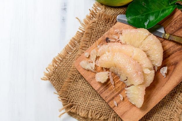 Pomelo ou pamplemousse pelé frais sur plaque de bois. fruits de saison de la thaïlande, pomelo ou agrumes grandis, pelés sur table en bois blanc