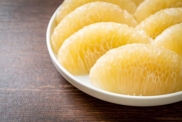 Pomelo, pamplemousse ou shaddock pelés frais sur plaque blanche
