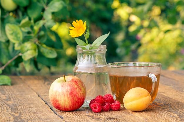 Pomme, abricot et framboises, fleur de calendula avec une tige dans un flacon en verre et tasse de thé vert.