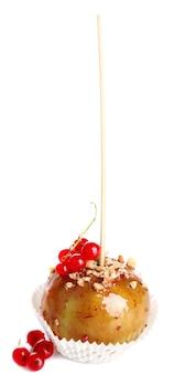 Pomme au caramel sucré sur bâton avec des baies, isolées sur blanc