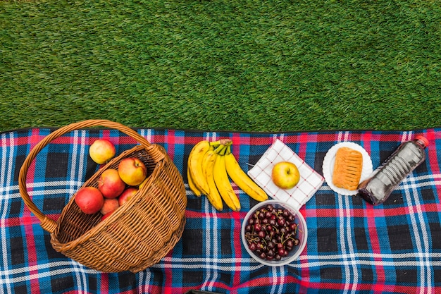 Pomme; banane; cerises; serviette et pâte feuilletée avec une bouteille d'eau sur la couverture sur l'herbe verte