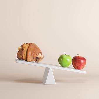 Une pomme basculant en bascule avec une cuisse de porc à l'extrémité opposée sur fond pastel.
