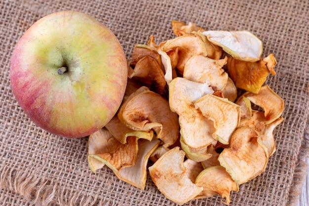 Pomme bio séchée maison tranchée sur fond de bois