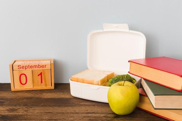 Pomme et boîte à lunch entre calendrier et livres