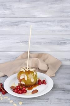 Pomme caramel sucré sur bâton avec baies, sur table en bois