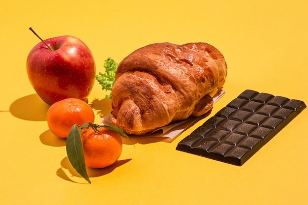 La pomme, le chocolat et les croissants sur jaune