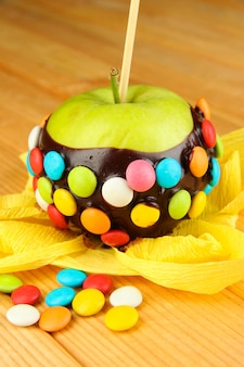 Pomme confite sur bâton sur table en bois