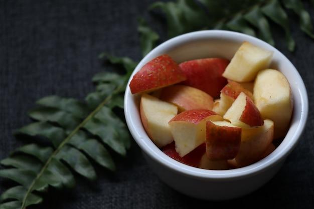 Pomme coupée dans un pot au fond d'une plante verte pomme rouge en morceaux côté espace pour l'écriture