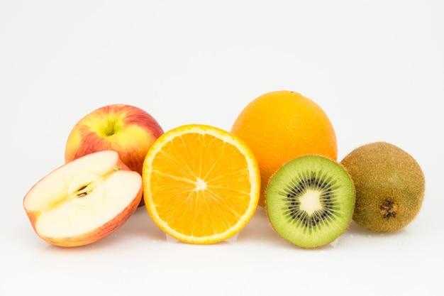 Pomme coupée à moitié isolée, orange et kiwi sur blanc.