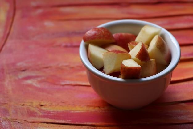 Pomme dans un pot sur fond rouge