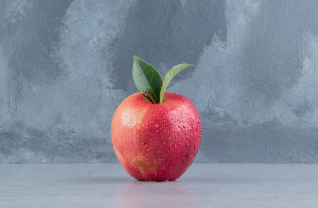 Une pomme délicieuse affichée sur du marbre.