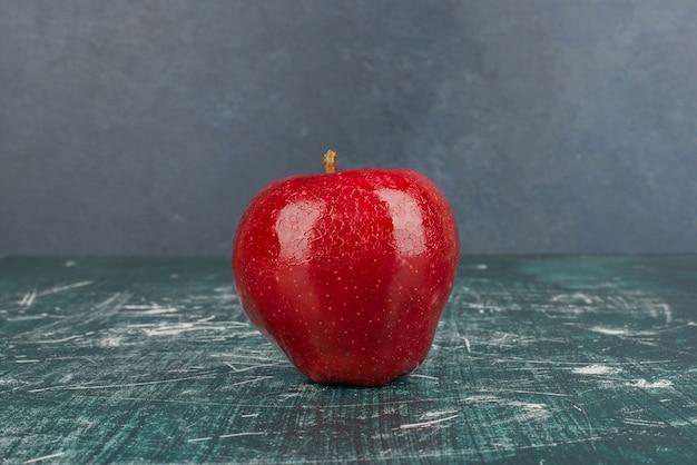 Pomme entière rouge sur fond bleu.