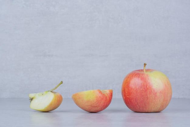 Une pomme entière avec des tranches sur fond blanc. photo de haute qualité