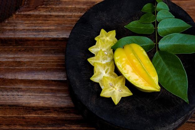 Pomme étoilée sur une planche à découper en bois tranche mûre le fruit placé sur des récipients en bois