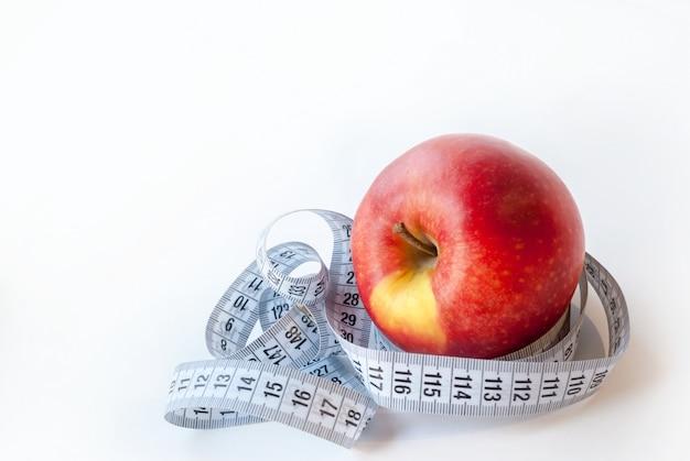 Pomme fraîche et ruban à mesurer sur fond blanc. concept de régime.