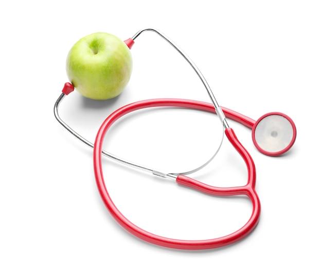 Pomme fraîche et stéthoscope sur blanc