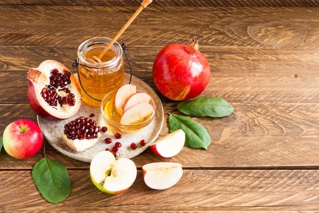 Pomme, grenade et miel, nourriture traditionnelle du nouvel an juif - rosh hashana. copiez le fond en bois de l'espace.