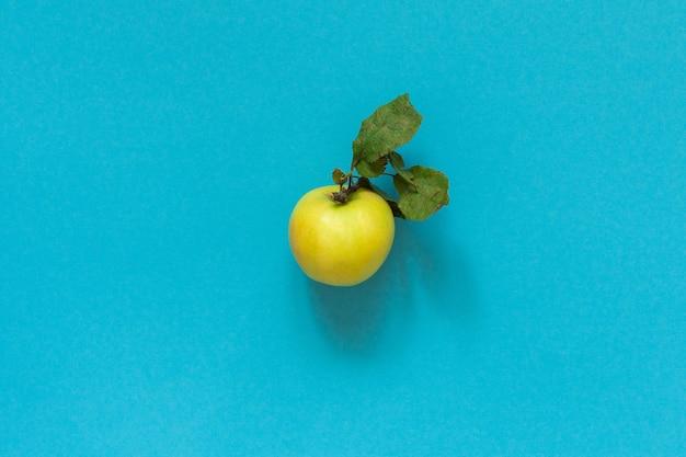Pomme jaune bio fraîche avec des feuilles au centre sur fond bleu