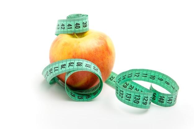 Pomme jaune et ruban à mesurer vert isolé sur blanc