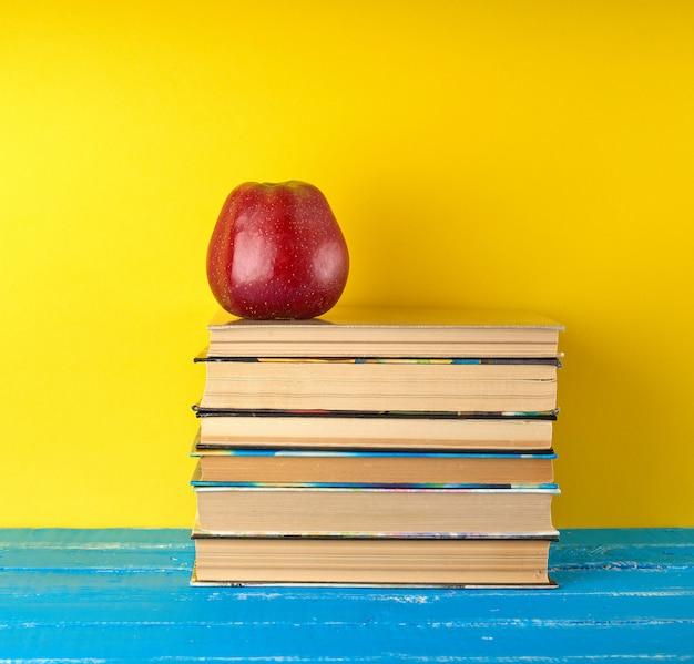 Pomme mûre rouge se trouve sur une pile de livres, fond jaune