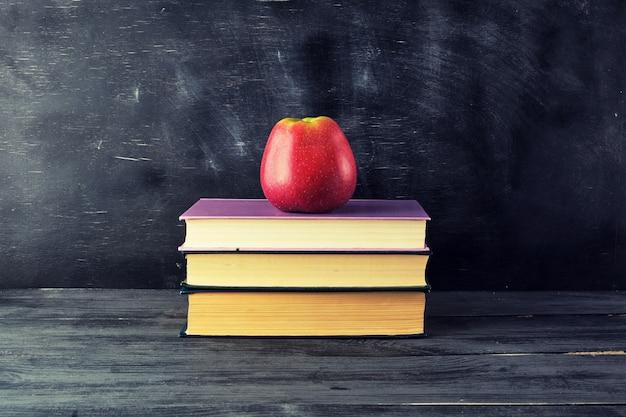 Pomme mûre rouge se trouve sur une pile de livres