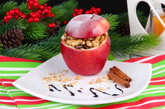 Pomme de noël farcie aux noix et raisins secs sur table sur fond sombre