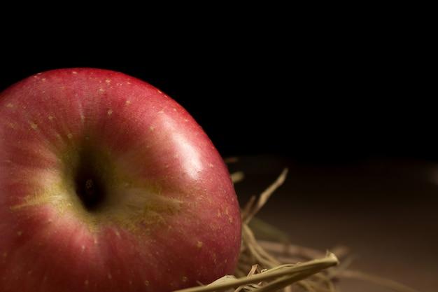 Pomme. paille. sur le bois. fond noir