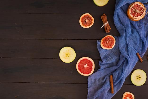 Pomme, pamplemousse et cannelle sur tissu bleu