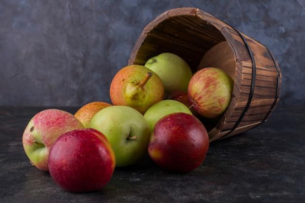 Pomme, pêche et poires dans un seau en bois