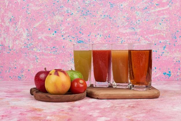 Pomme et pêches avec des verres de jus colorés.