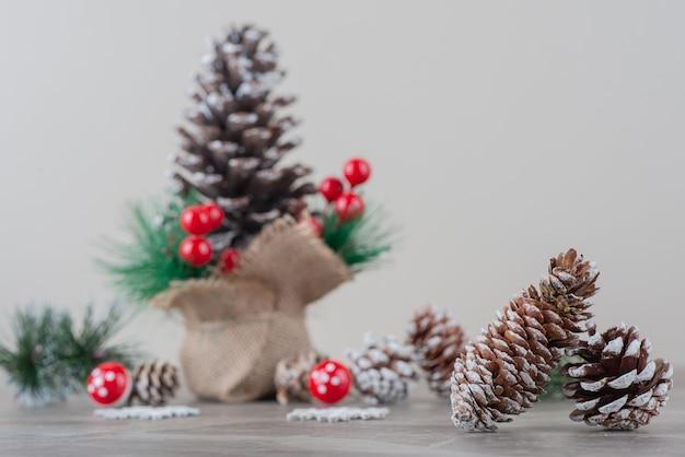 Pomme de pin décorée de baies de houx et de branches sur table en marbre
