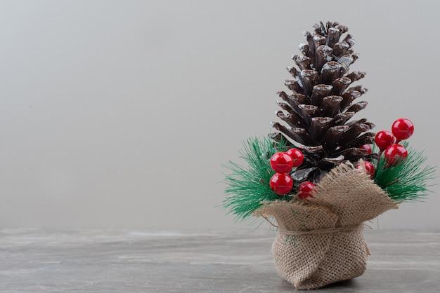 Pomme de pin décorée de baies de houx et de branches sur table en marbre.