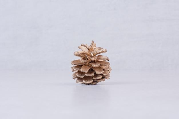 Une pomme de pin dorée sur une surface blanche