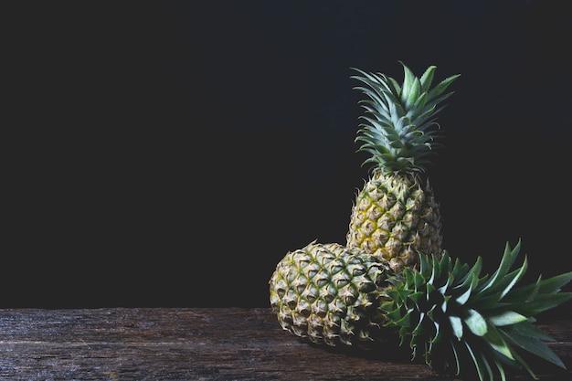 Pomme de pin frais, vitamine et bonne pour la santé sur une table en bois avec un fond noir.