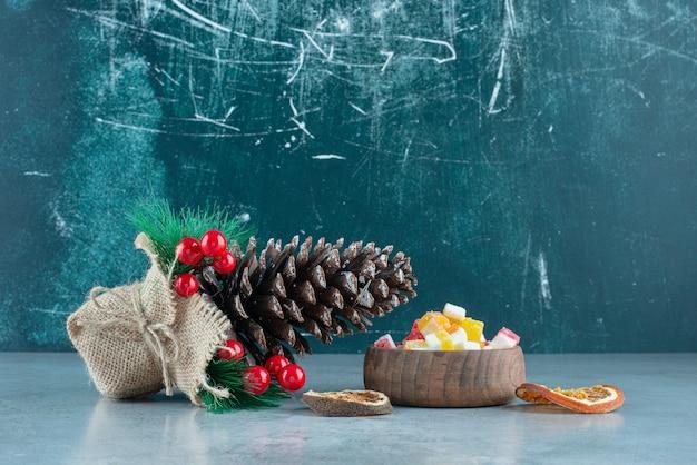 Une pomme de pin de noël avec des oranges séchées et un bol de bonbons en bois.