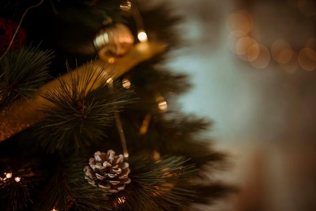 Pomme de pin sur sapin décoré de guirlande et de boules