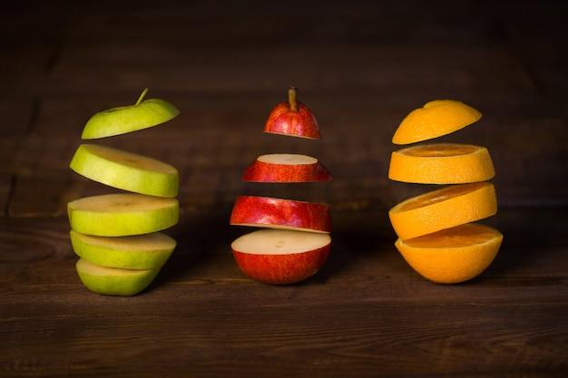 Pomme, poire, orange coupées en deux figées dans l'air sur une table en bois noire