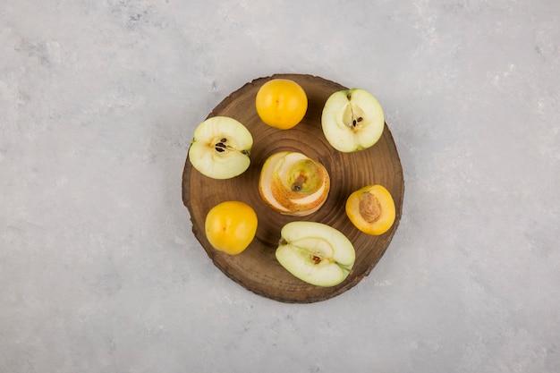 Pomme, poire et pêches sur un morceau de bois au milieu