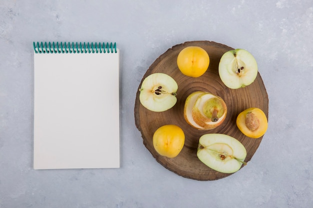 Pomme, poire et pêches sur un morceau de bois, avec un cahier de côté