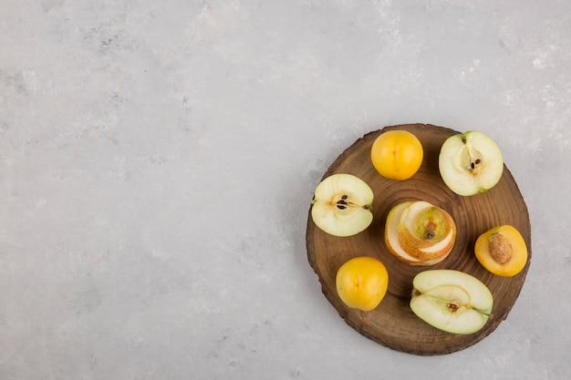 Pomme, poire et pêches sur un morceau de bois, vue du dessus