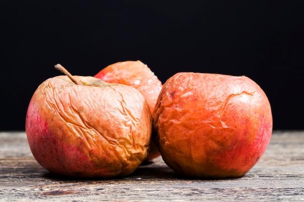 Une pomme pourrie couverte de moisissure et de moisissure, de nourriture avariée, de champignons et de moisissures a détruit une pomme mûre lors d'une violation de stockage