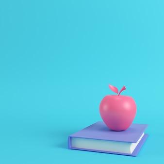 Pomme rose sur un livre sur fond bleu clair
