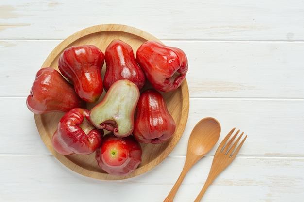 Pomme rose sur une surface en bois blanche