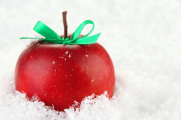 Pomme rouge avec archet dans la neige se bouchent