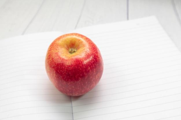 Pomme rouge sur le cahier