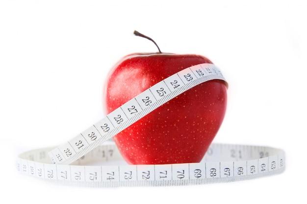 Pomme rouge avec centimètre sur fond blanc. isolé sur blanc. alimentation saine